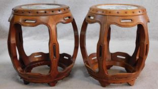 A pair of Chinese carved and pierced hardwood barrel stools with inset hand painted porcelain tile