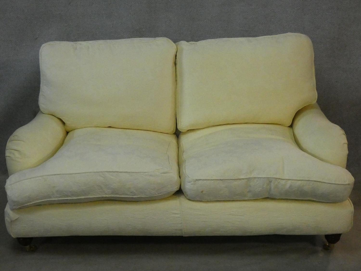 A Multiyork Howard style two seater sofa in jacquard upholstery on turned tapering supports on brass