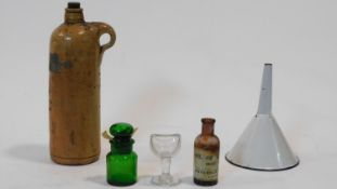 A collection of antique pharmaceutical items. Including a clear glass stemmed eye bath, a white