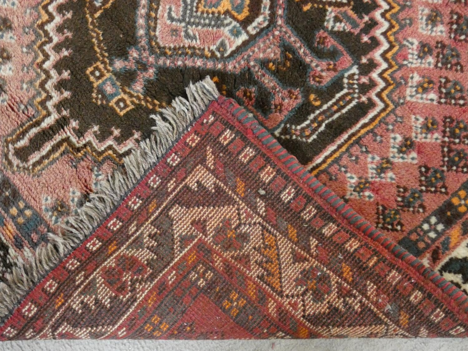 An Eastern rug with double stepped lozenge medallions on a blush ground within stylised floral - Image 4 of 4