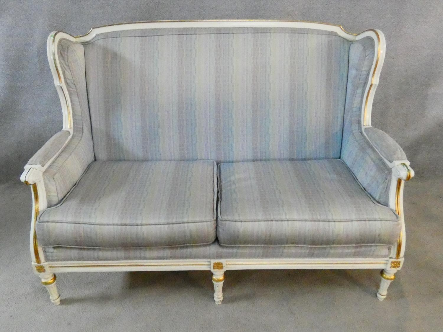 A Louis XVI style gilt and with painted two seater sofa in pale damask upholstery. H.93 L.136 D.77cm