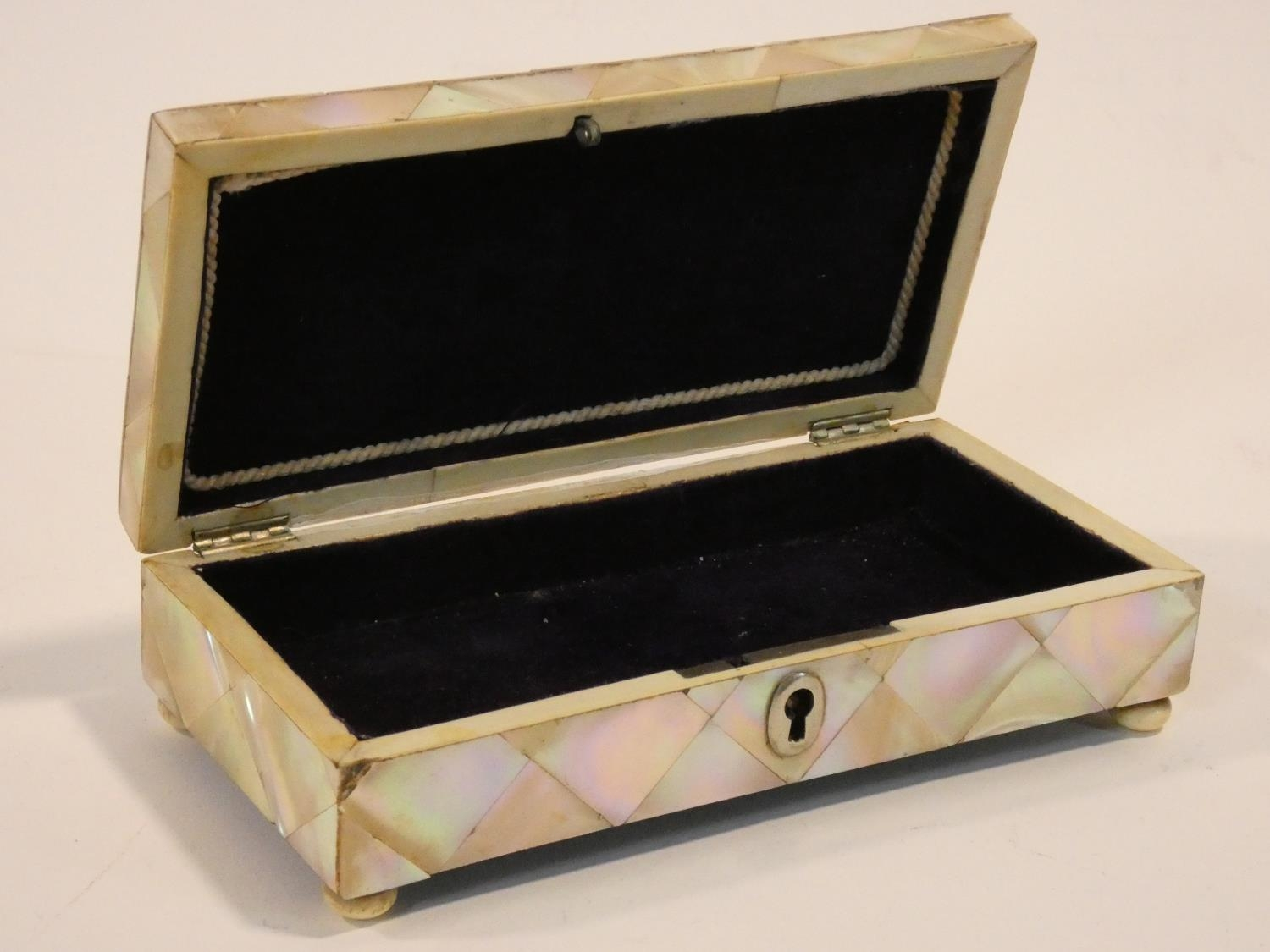 A 19th century parquetry inlaid mother of pearl jewellery casket on ivory bun feet. Missing key. H.