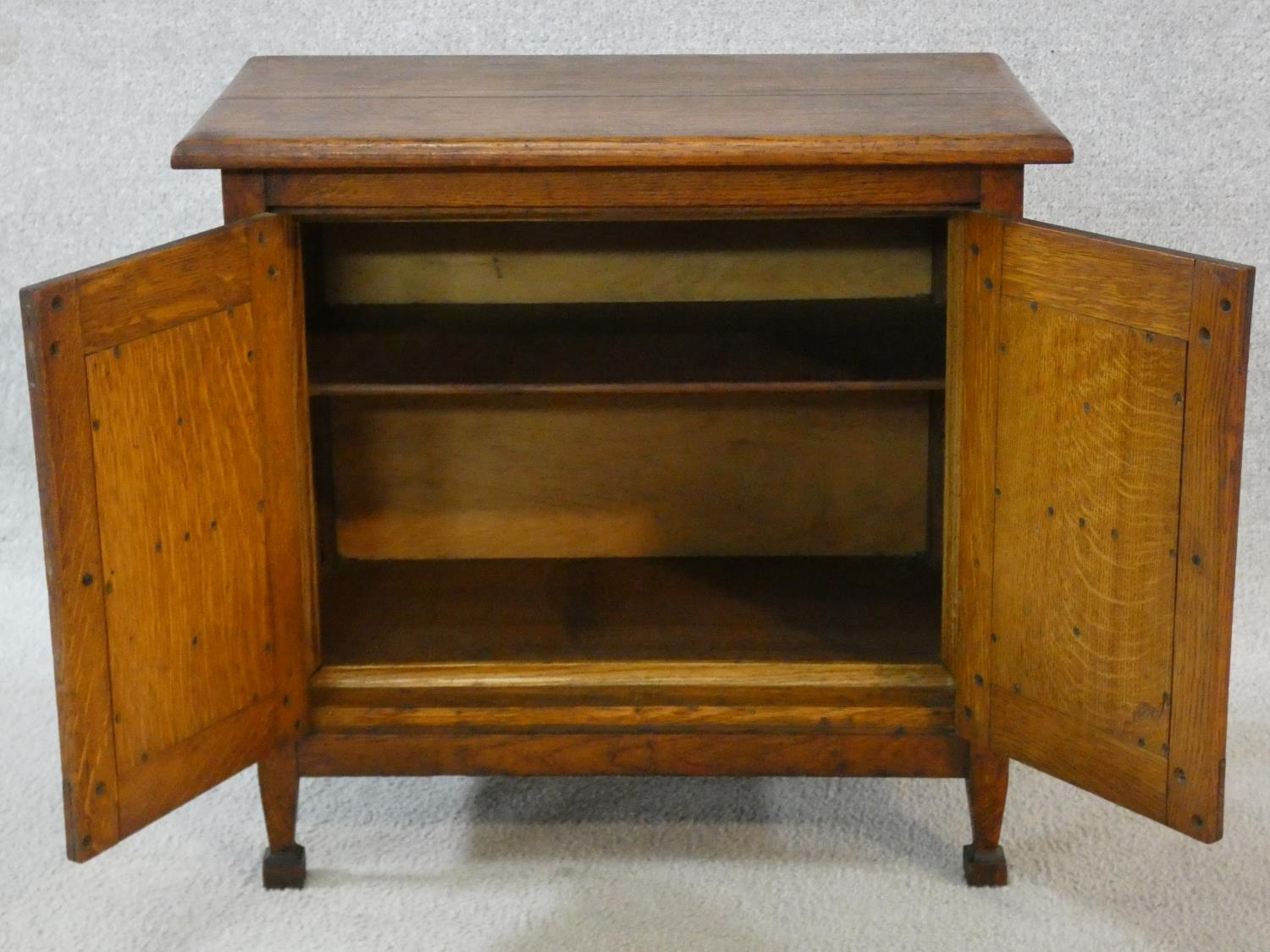 An early 20th century country oak style side cabinet with carved panel doors on squat square - Image 14 of 14