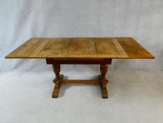 A mid century Jacobean style oak draw leaf dining table on stretchered baluster base. H.75 L.121 (
