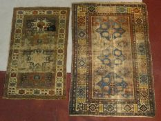 An Eastern rug with triple diamond medallions within multi borders and a similar rug with