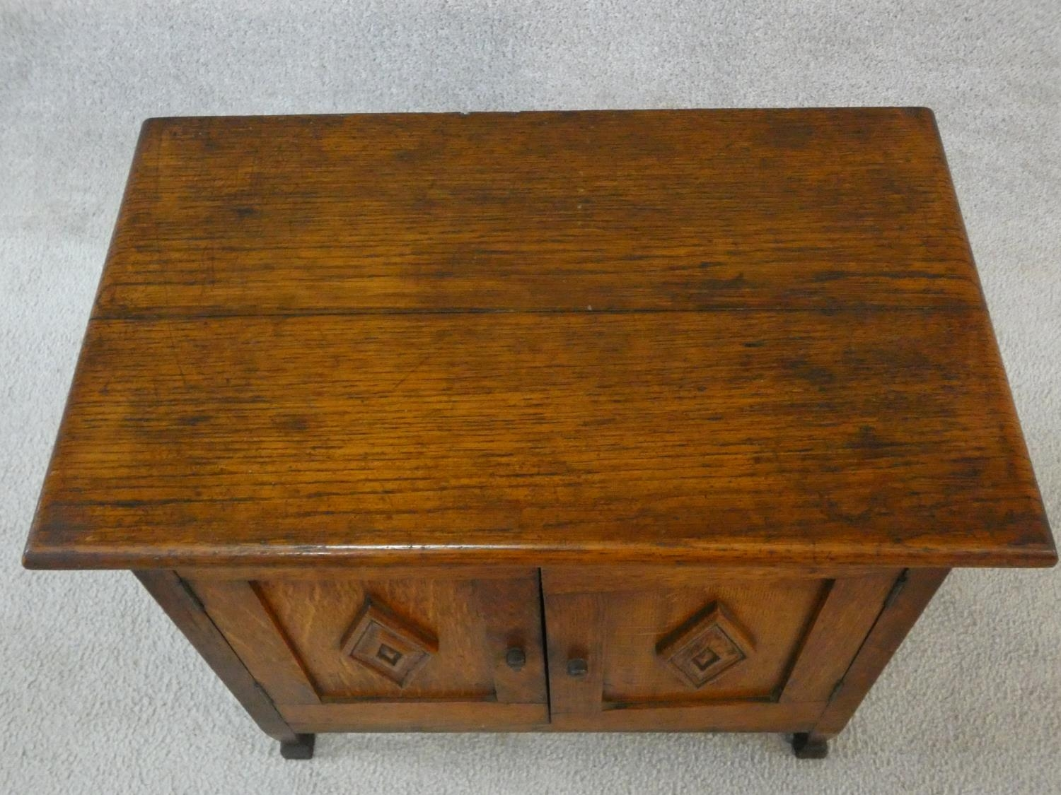 An early 20th century country oak style side cabinet with carved panel doors on squat square - Image 6 of 14