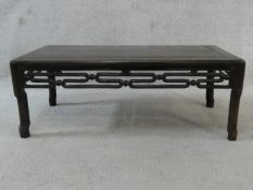 A Chinese hardwood low table with carved and pierced frieze on shaped supports. H.27 L.72 W.38cm