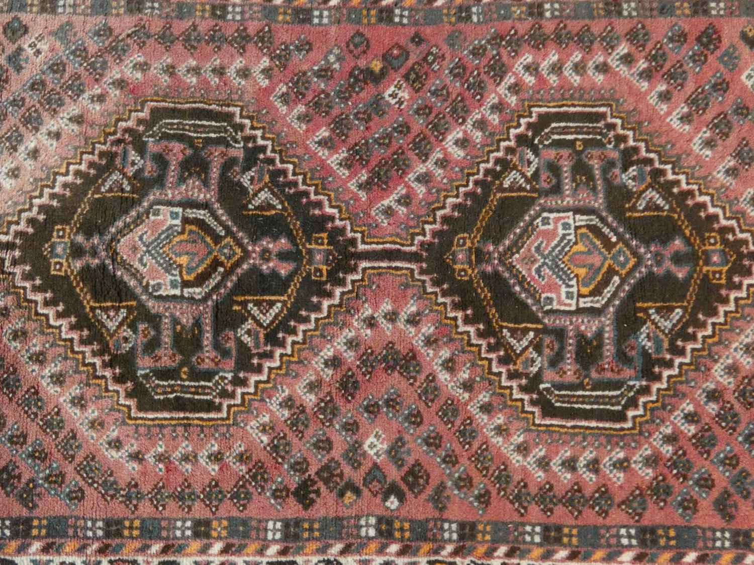 An Eastern rug with double stepped lozenge medallions on a blush ground within stylised floral - Image 2 of 4