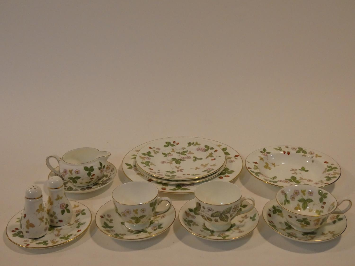 A Wedgwood Wild Strawberry pattern part tea service. Including three cups and saucers, salt and