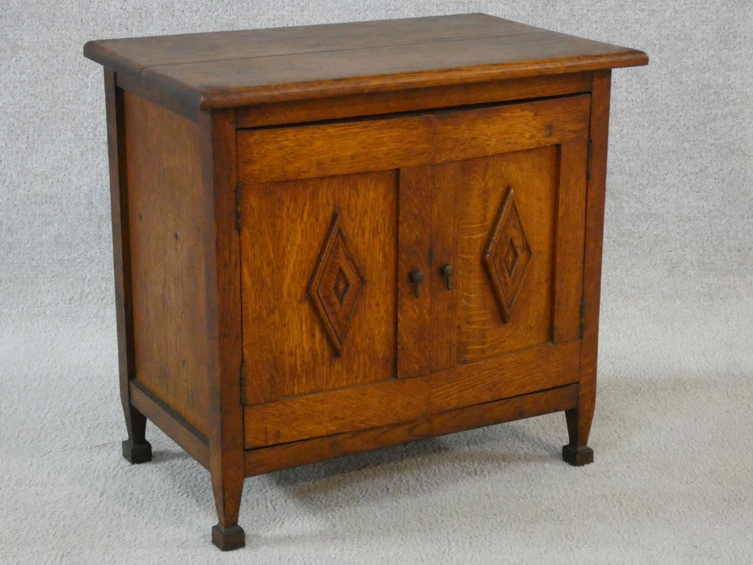 An early 20th century country oak style side cabinet with carved panel doors on squat square - Image 4 of 14