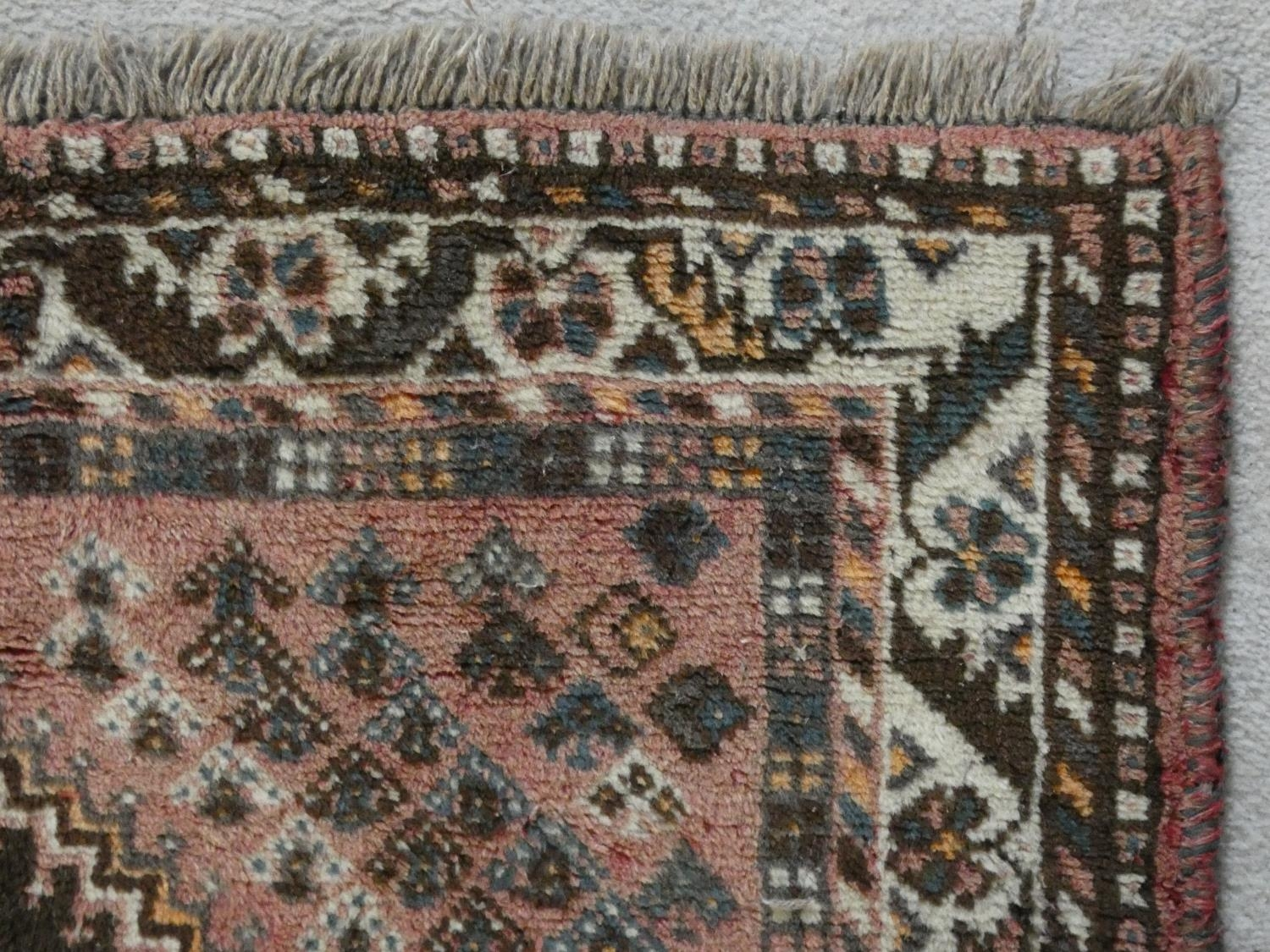 An Eastern rug with double stepped lozenge medallions on a blush ground within stylised floral - Image 3 of 4