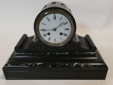 An early 19th century marble and slate mantel clock with Roman numerals on a white enamel dial. H.