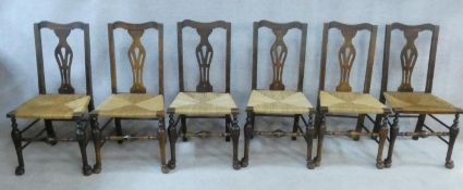 A set of six 19th century country oak dining chairs with pierced splat backs above woven rush