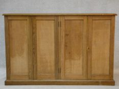 A late 19th century oak estate cabinet with two pairs of panel doors enclosing a fitted interior
