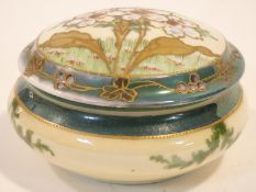 An antique hand painted and gilded porcelain lidded trinket box. The lid decorated with stylised