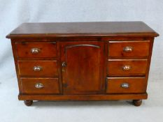A late 19th century pine dresser with central panel door flanked by drawers on bun feet. H.84xW.