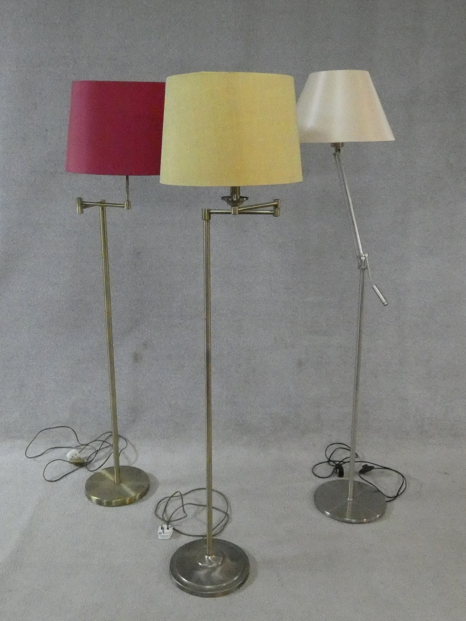 Two brass standard lamps with articulated actions and a chrome adjustable standard lamp. H.162cm