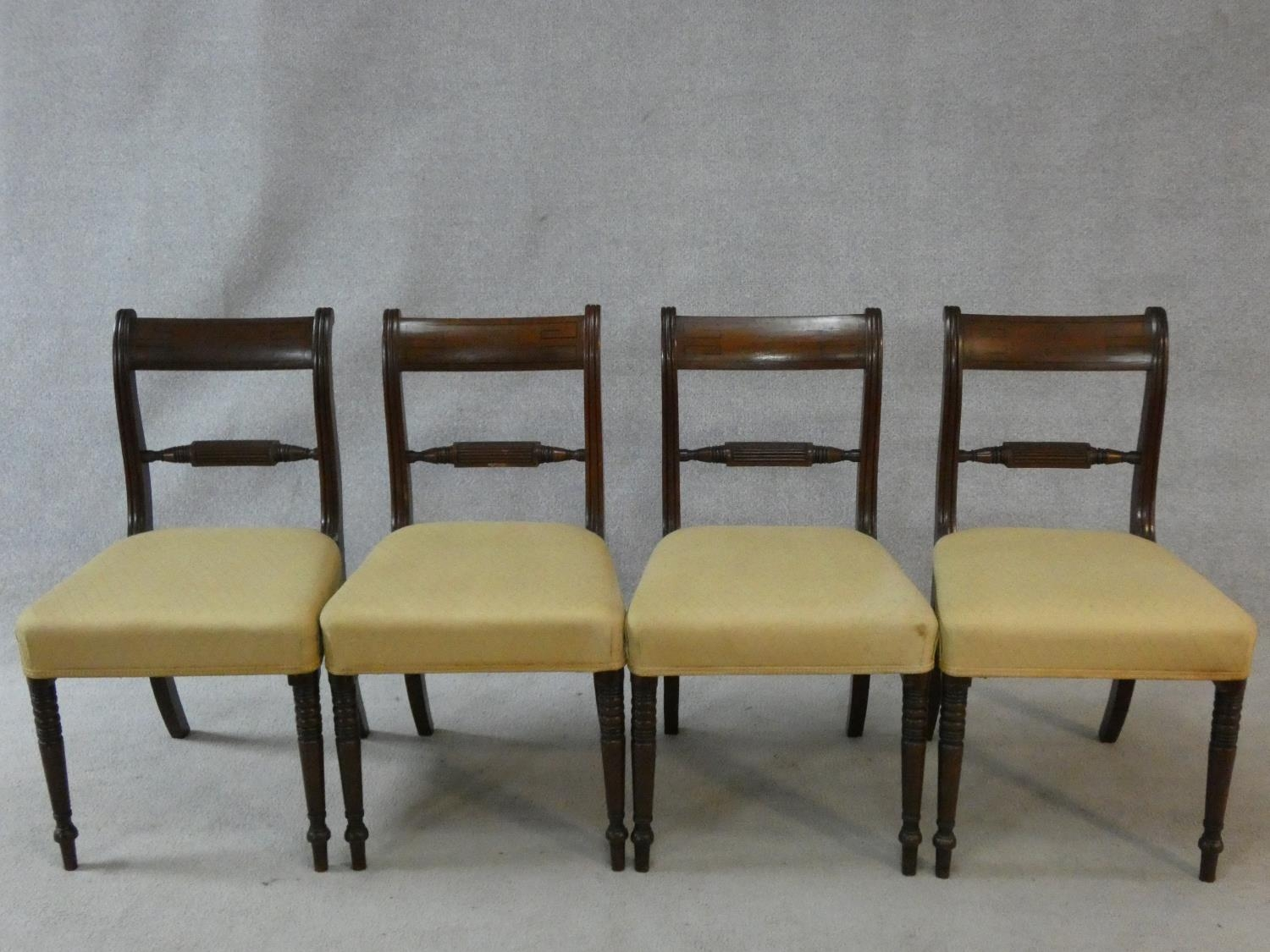 A set of four late Georgian mahogany bar back dining chairs with ebony Greek key pattern inlay above