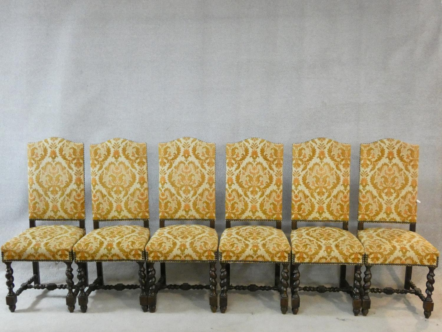 A set of six Jacobean style oak framed high back dining chairs in gold cut floral upholstery on