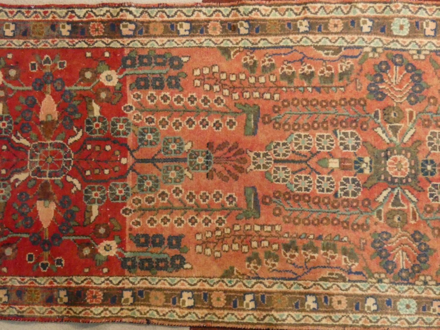 An Eastern runner with repeating floral medallions on a madder field within stylised multiple - Image 3 of 5