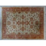 A Ziegler style rug with repeating scrolling floral design across a fawn field within floral