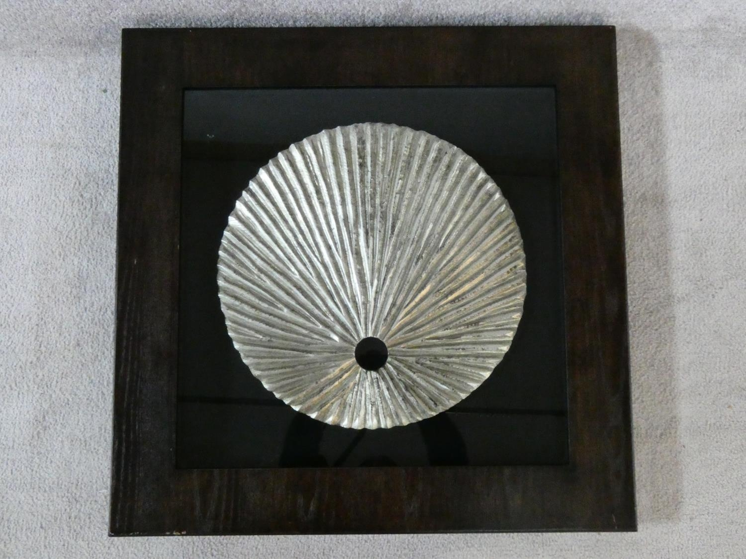 A contemporary carved wood textured silver disk, mounted on black, shadow box framed. H.80 W.80cm