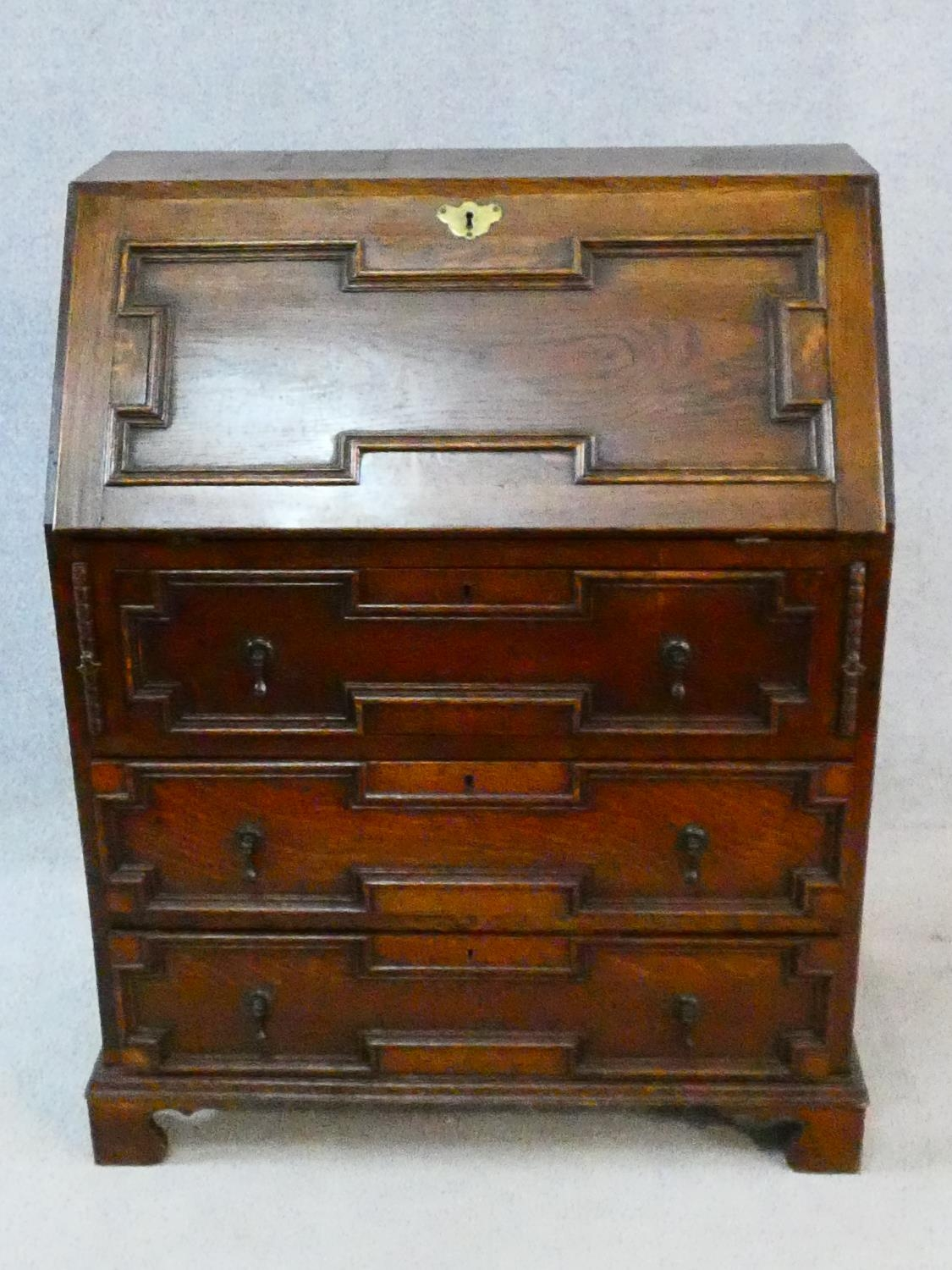 A mid century Jacobean style oak bureau with lozenge inset panels and fall front revealing fitted