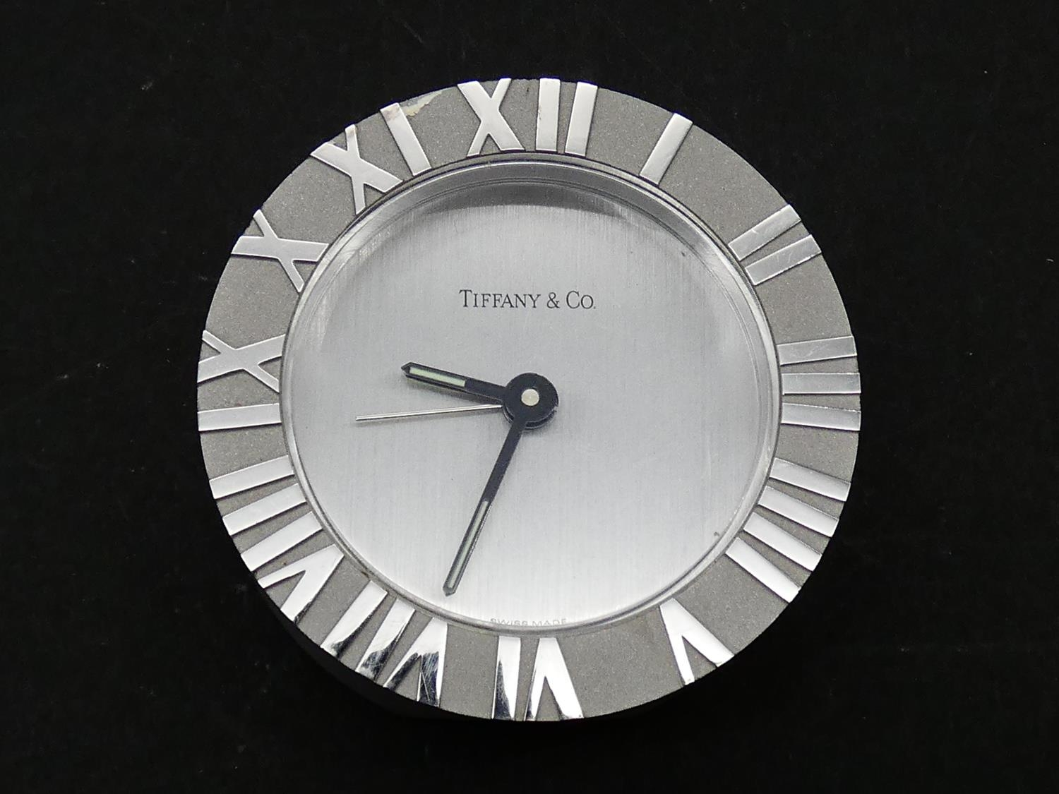 A Tiffany & Co Swiss made stainless steel Roman numeral quartz alarm clock with brushed chrome bezel