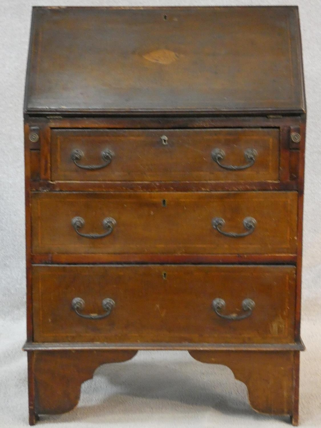 An Edwardian mahogany bureau with satinwood stringing and shell inlay to the frieze. H.95 W.61 D.