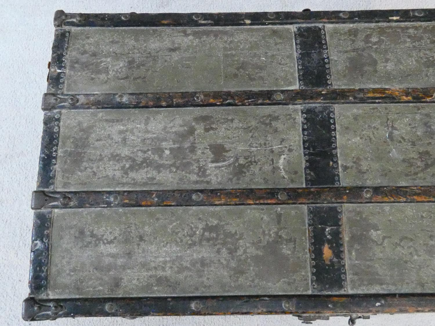 A vintage metal bound lidded travelling trunk with twin iron carrying handles. H.32xW.92xD.53cm - Image 4 of 8