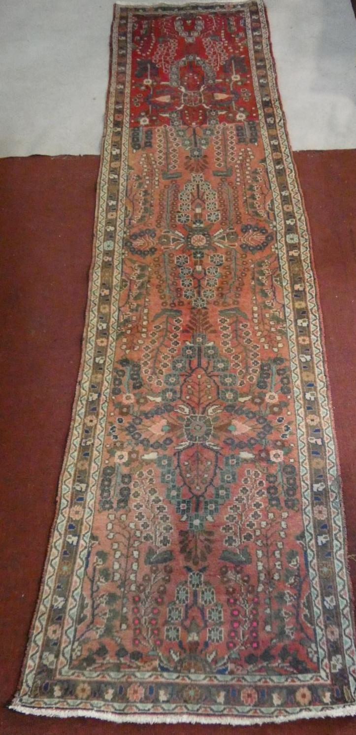 An Eastern runner with repeating floral medallions on a madder field within stylised multiple