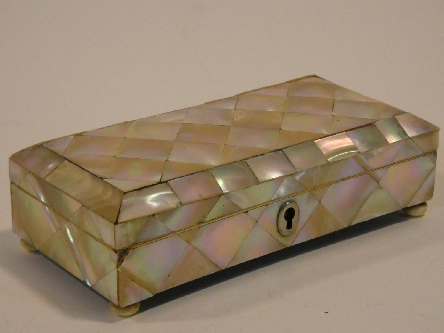 A 19th century parquetry inlaid mother of pearl jewellery casket on ivory bun feet. Missing key. H. - Image 3 of 5