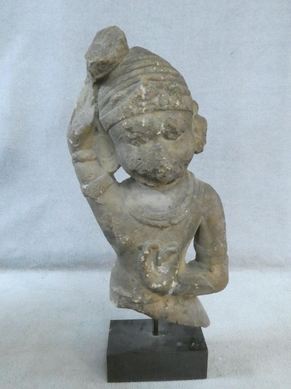 A 14th/15th century South East Asian carved sandstone figure of a deity mounted on a square