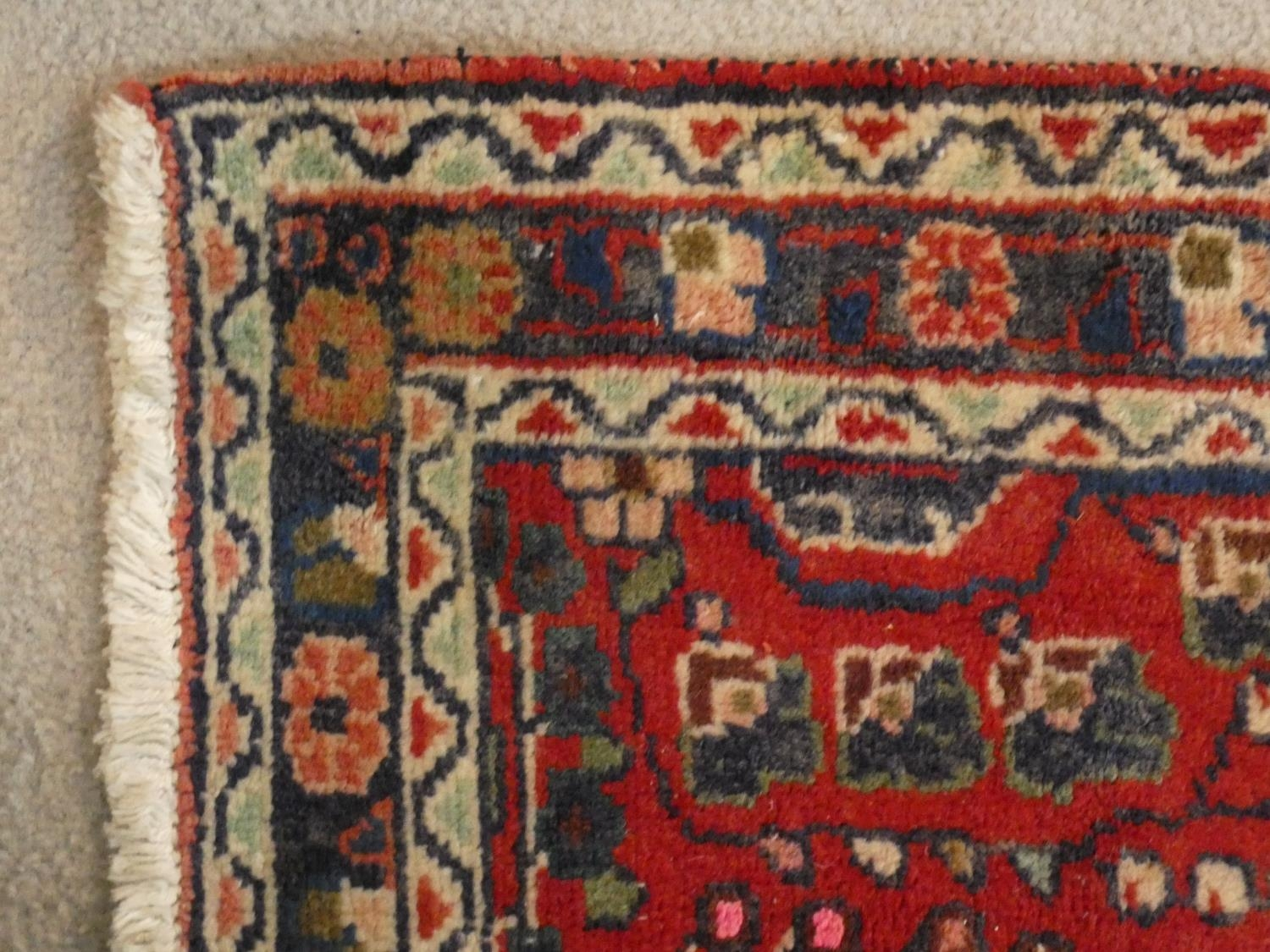 An Eastern runner with repeating floral medallions on a madder field within stylised multiple - Image 4 of 5