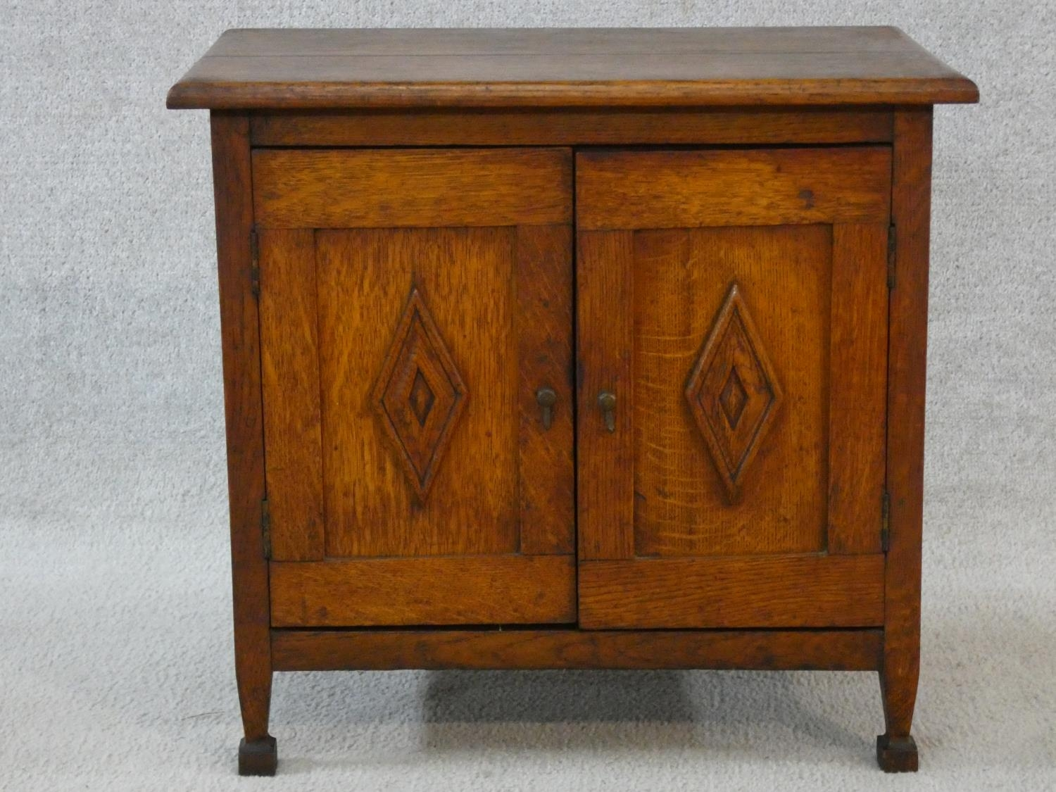 An early 20th century country oak style side cabinet with carved panel doors on squat square