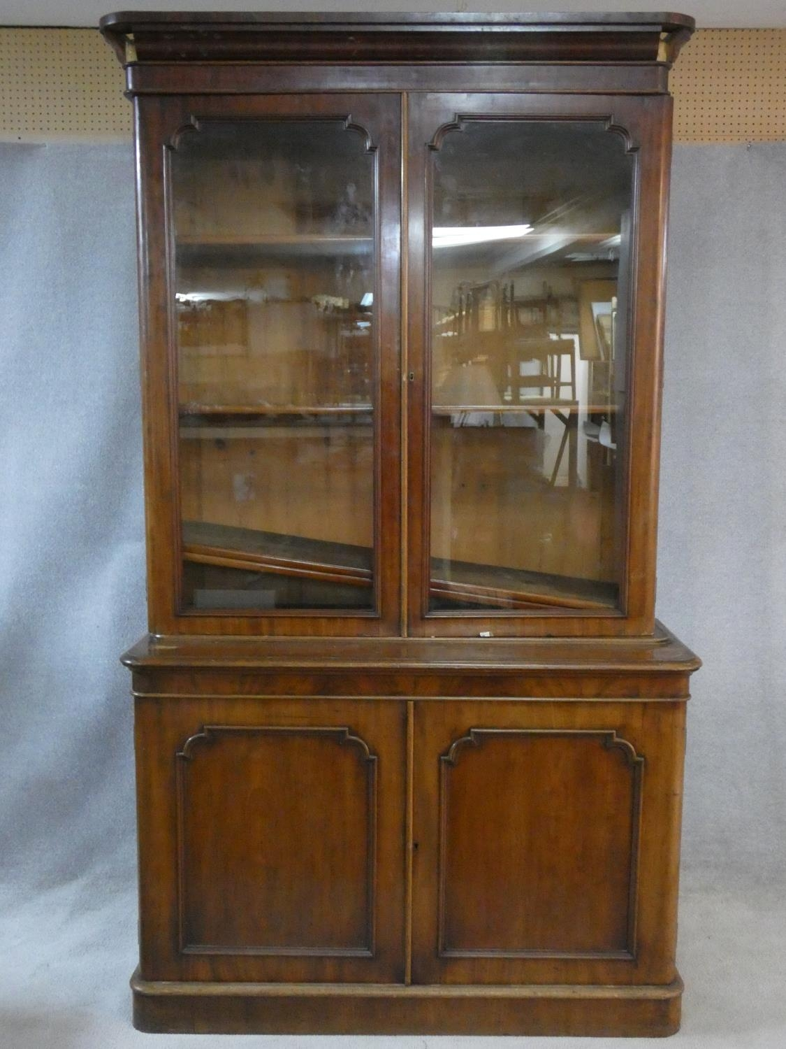 A Victorian mahogany library bookcase with upper glazed doors enclosing book shelves above base