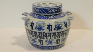 A blue and white Chinese Sanskrit ceramic burial jar with cover decorated with waves and eight