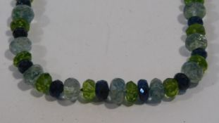 A bespoke faceted Apatite, Aquamarine and Peridot bead necklace with a silk chord loop clasp. L.42cm