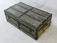 A vintage metal bound lidded travelling trunk with twin iron carrying handles. H.32xW.92xD.53cm