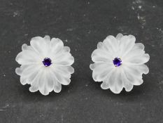 A pair of carved rock crystal daisy earrings each set to centre with a round brilliant cut