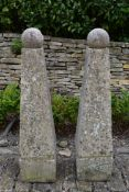 A pair of large weathered reconstituted stone garden obelisks topped with removable spheres. H.132cm