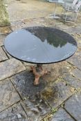 A polished marble topped conservatory or garden table on cast iron entwined Trafalgar Dolphin
