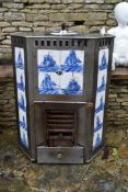 A late 19th century Dutch steel free standing fireplace with inset blue and white sailboat tiles