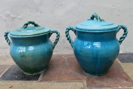 A pair of Eastern turquoise glazed lidded storage pots with twin rope design handles. H.47 x Dia.