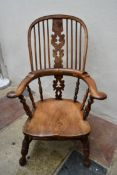 An antique yew and elm Windsor armchair with carved and pierced splat on turned and stretchered