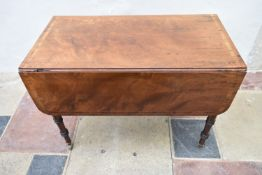 A Regency figured mahogany and rosewood crossbanded Pembroke table on ring turned tapering