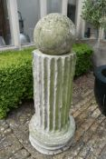 A moulded concrete classical column style plinth with weathered spherical finial. H.128cm