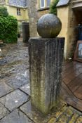 A carved stone garden plinth with weathered stone spherical finial. H.120xW.50cm