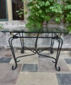 A wrought iron conservatory dining table with bevelled plate glass top. H.73xW.115cm