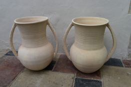A pair of Persian earthenware twin handled urns of bulbous form. H.66cm